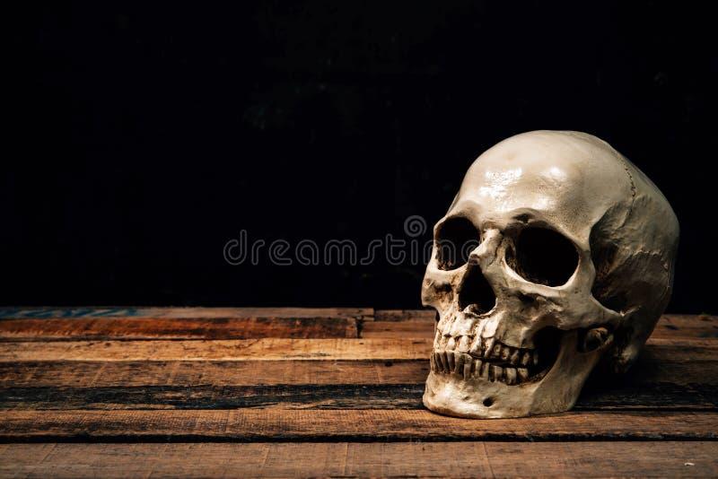 Cranio umano su vecchio fondo di legno immagine stock libera da diritti