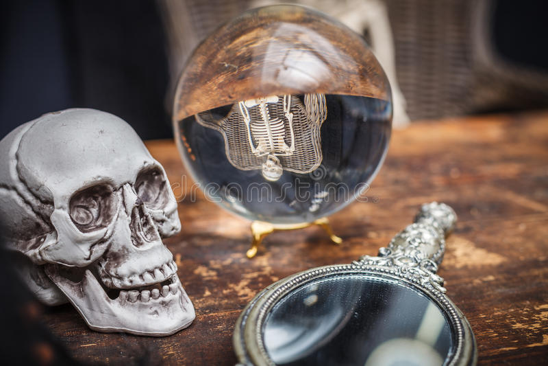 Cranio, vecchio specchio e sfera di cristallo con lo scheletro di riflessione fotografie stock