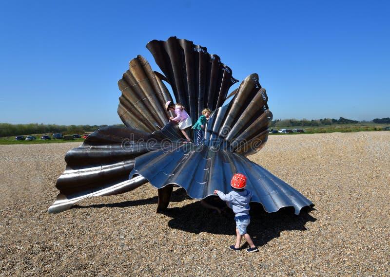 Crantez Shell Sculpture sur la plage d'Aldeburgh avec des enfants s'élevant là-dessus photos stock