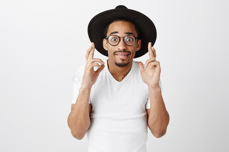 Crap, hope that nobody will notice. Worried handsome young african-american male in black hat and white t-shirt, raising royalty free stock photos