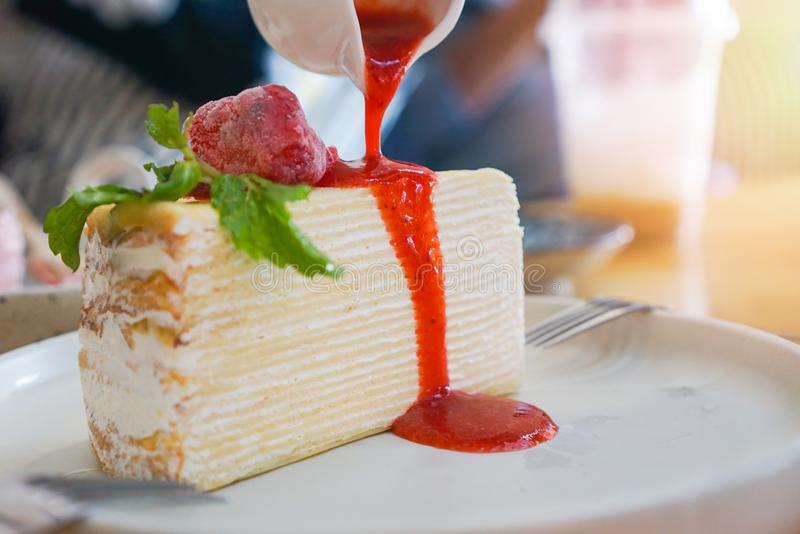 Crape cake slice with strawberry sauce on white plate on the table background - Piece of cake with whipped cream stock photography
