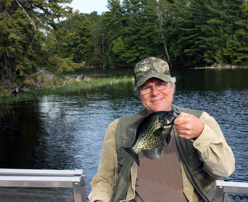 Crappie caught by fisherman. Fisherman holding a crappie caught on a freshwater lake stock photo