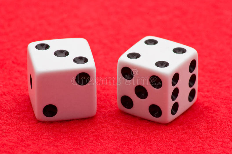 Craps. Two white dice displaying craps seven on two sides on red felt background royalty free stock photos