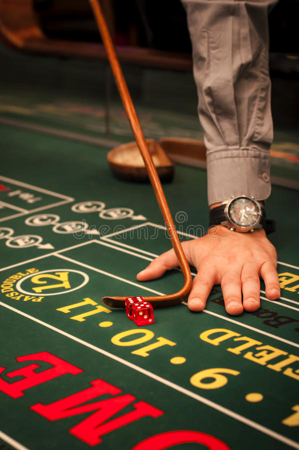 Craps dealer. Casino dealer pushing a pair of dice on a craps table stock photos