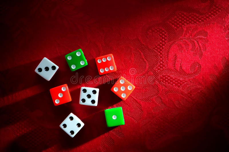 Craps Dice for Shooting Gambling Game. Gambling craps game dice used for shooting and rolling with bet wager on roll over luxurious red damask fabric in a classy royalty free stock images