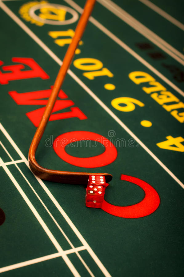 Craps table. Casino dealer pushing a pair of dice on a craps table stock images
