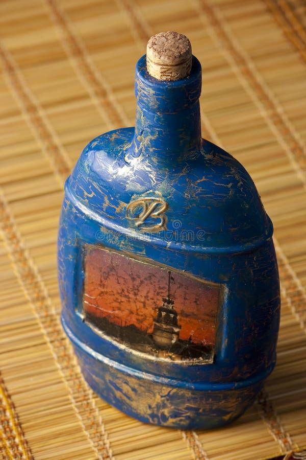 Craquelure decoupage bottle on a mat. Craquelure decoupage bottle on a chinese mat stock images