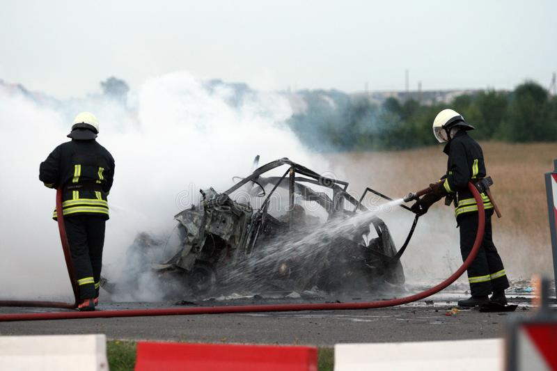 Crash on a motorway firefighters extinguish a burning car stock images