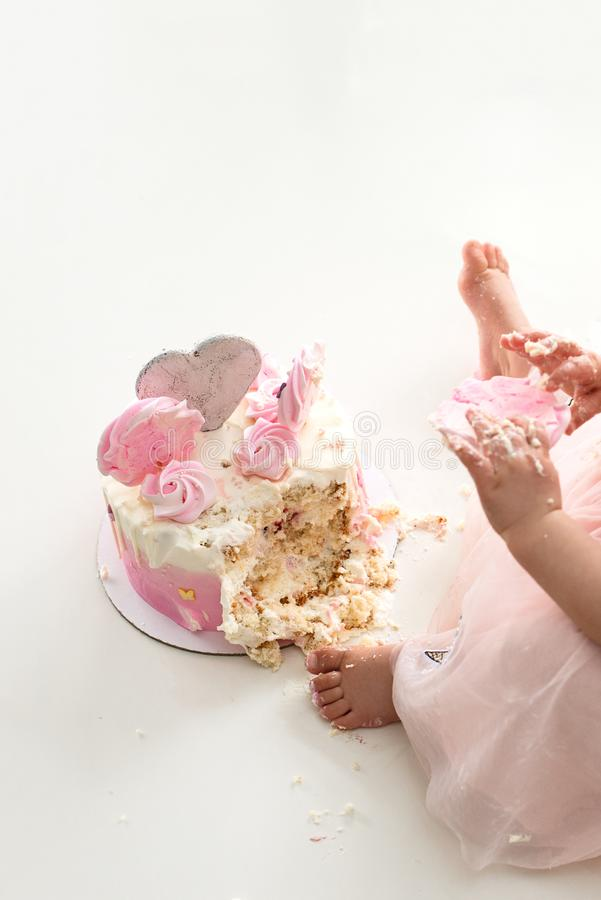 Crash pink cake at the celebration of the first birthday of the girl, ruined sponge cake, broken marshmallow, baby hands and lags. Permissiveness, disobedience stock images