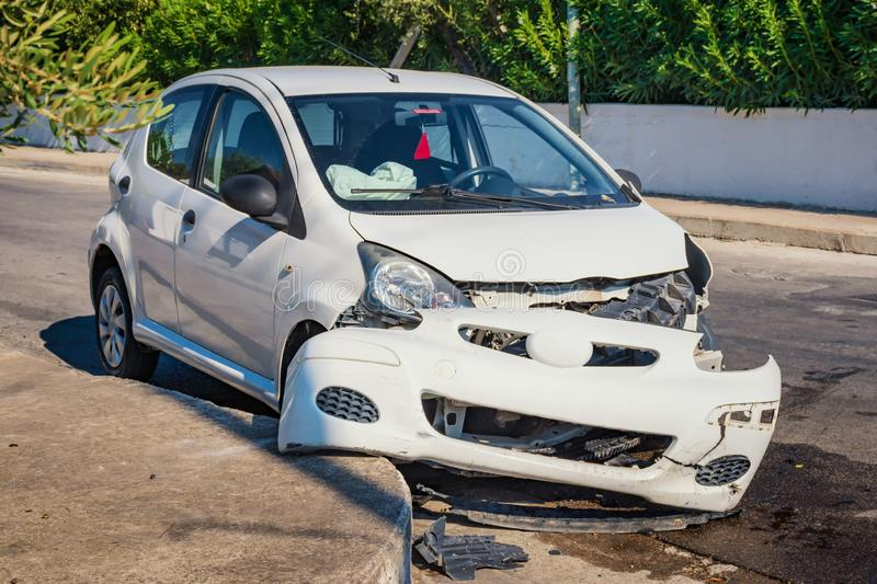 Crashed car after accident with deflated airbags on road in city. Sunny day stock photography