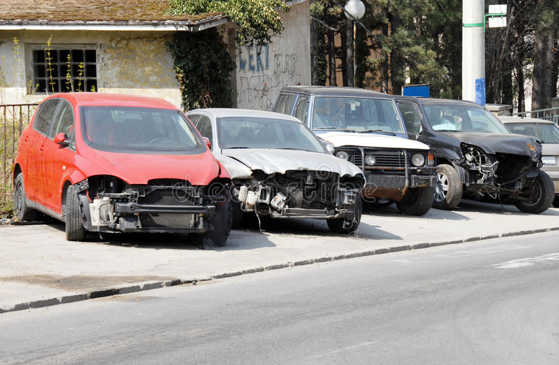 Crashed cars parked. Four various crashed cars parked on sidewalk royalty free stock photo
