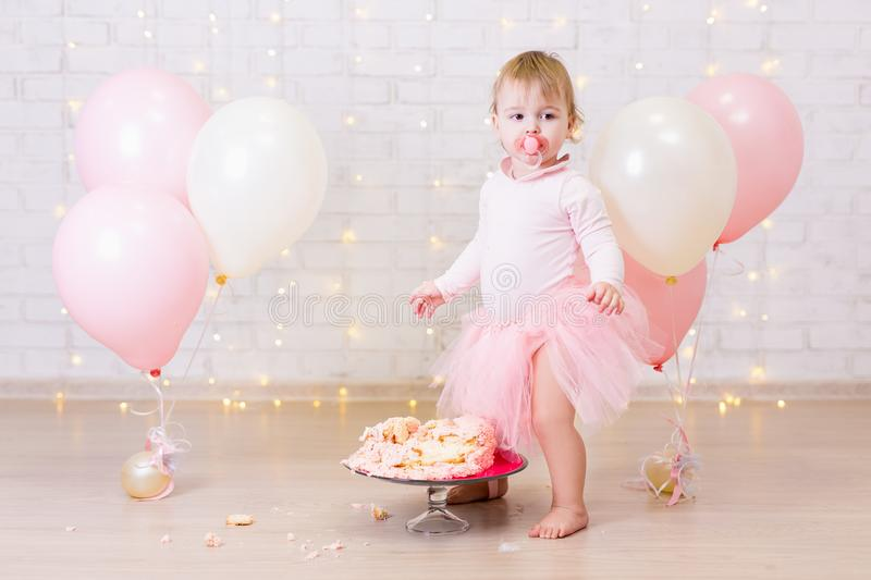 crashed party background - cute little girl and smashed cake over brick wall with lights and balloons stock photos