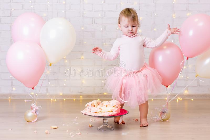 crashed party background - little girl and smashed cake over brick wall with lights and balloons stock image