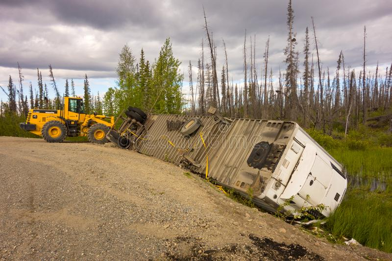 A crashed semi trailer on the cassiar highway. A tractor helping at the scene of an accident in northern canada stock photos