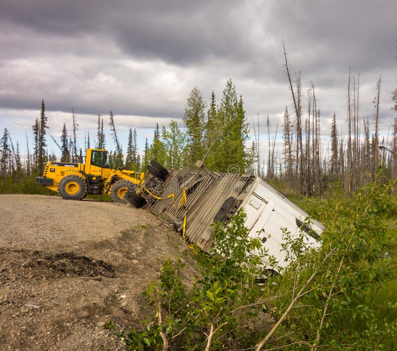 A crashed semi trailer on the cassiar highway. A tractor helping at the scene of an accident in northern canada stock image