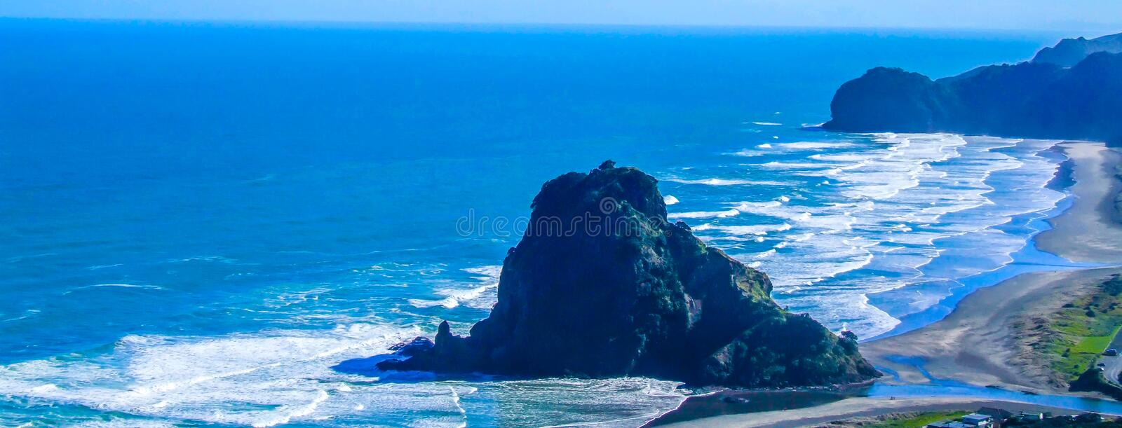 Piha Beach, north Island, auckland, New Zealand. Crashing oceans, high waves, surfing, rock formations, rock out crops, beaches, lion rock royalty free stock image