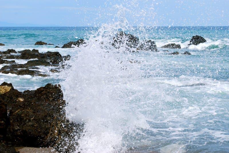 The crashing surf hits volcanic rock causing beautiful spray royalty free stock photography