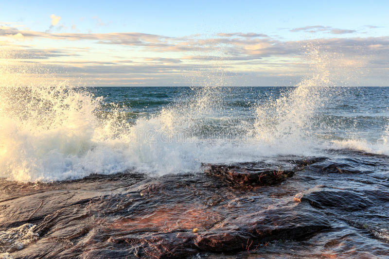 Crashing Wave on Lake Superior at Pictured Rocks National Lakeshore. Storm surge drives crashing waves over sandstone rock at Pictured Rocks National Lakeshore royalty free stock photos