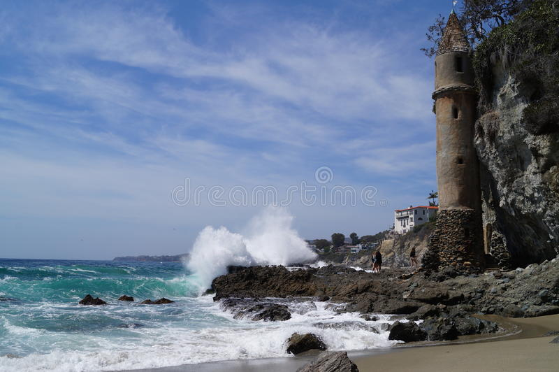 Crashing waves on rocky beach with small victorian castle on side of cliff royalty free stock photography