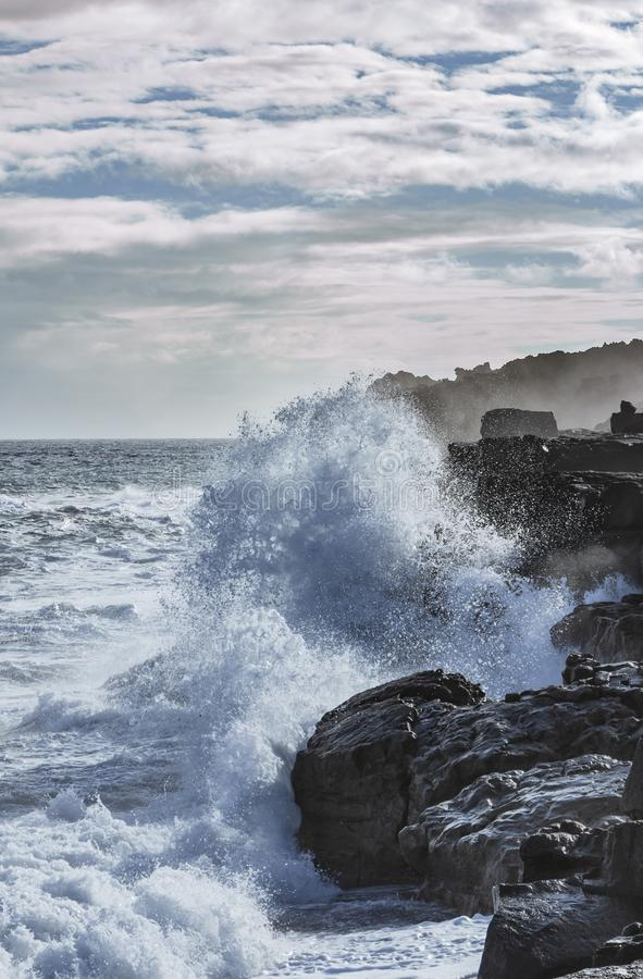 Crashing waves on rocky shore - color. Seawaves crash against the black volcanic rocks on a beach at big island hawaii  cloudy color crashing day force rocky stock photos