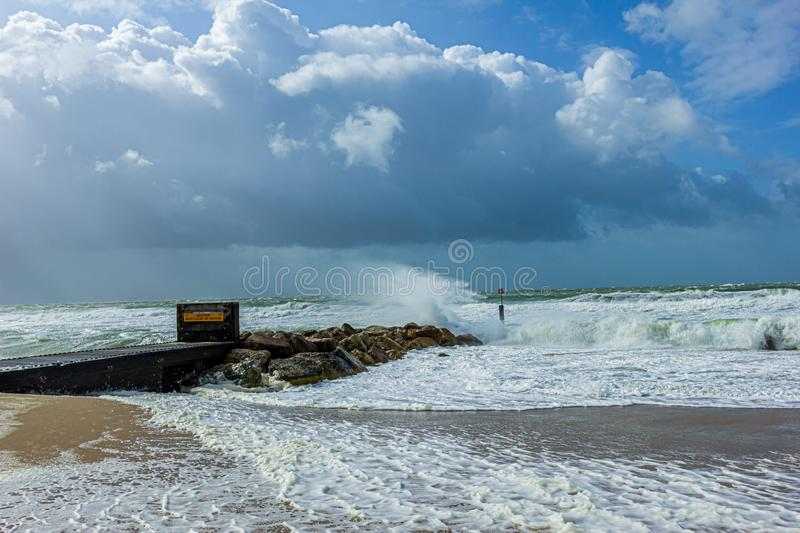 Crashing waves on a stony groyne breakwater during a massive storm under a majestic blue sky and white clouds stock image