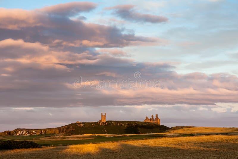 CRASTER, NORTHUMBERLAND/UK - 20-ОЕ АВГУСТА: Заход солнца над Dunstanburg стоковые изображения