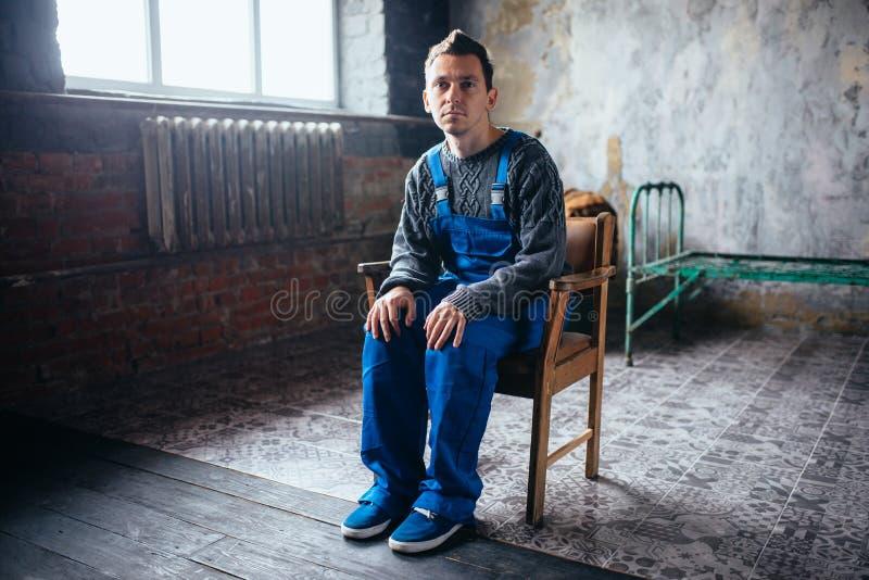 Crasy mężczyzna obsiadanie w krześle, psychiczny pacjent zdjęcie royalty free