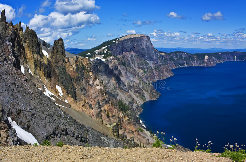 Crater Lake grandeur. Crater Lake panorama (with western pasque flower anemone puffs) at Watchman Overlook, Oregon stock photo