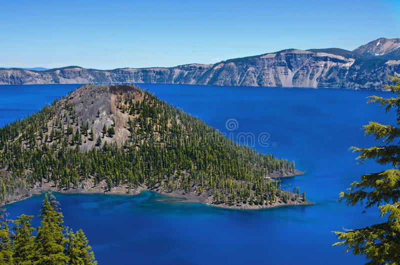 Crater Lake National Park, Oregon. Tree lined Wizard Island is surrounded by the vibrant blue waters of Crater Lake in Crater Lake National Park, in Oregon, on royalty free stock image