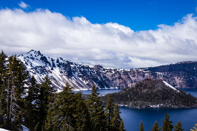 Crater Lake and Wizard Island. With clouds. The Blue water of Crater Lake never ceases to amaze, and today it matched the deep blue sky royalty free stock photo