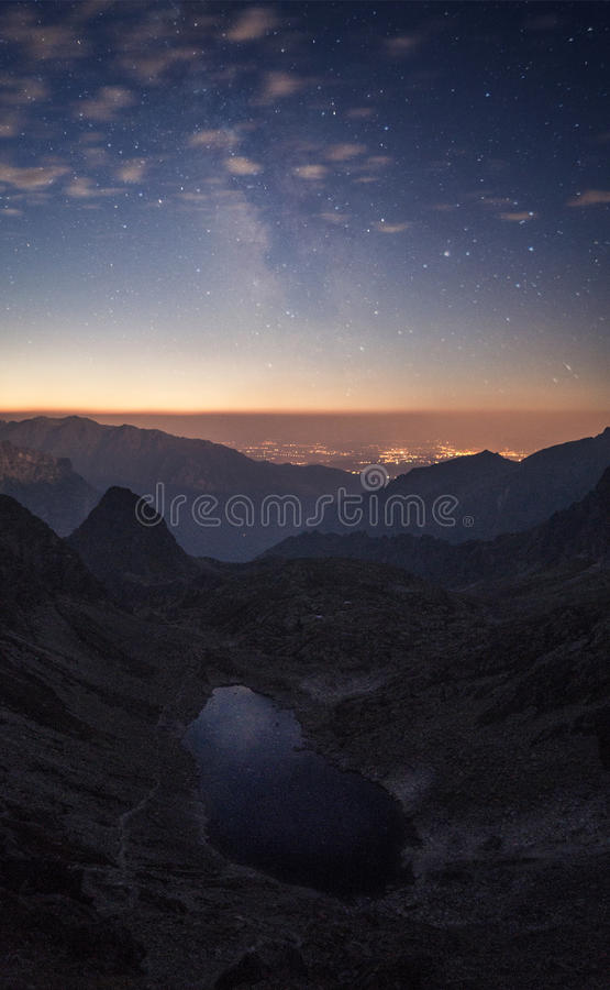 Crater Between Mountains Under Blue Sky White Clouds and Stars during Sunset royalty free stock photography