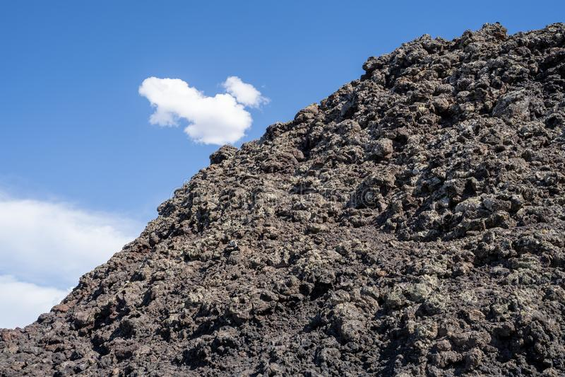 Craters of the Moon National Monument - black lava rock against blue sky stock photos