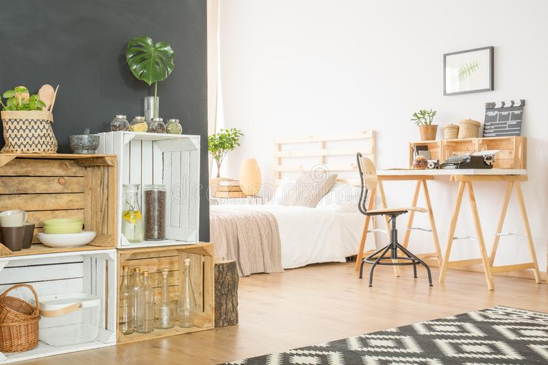 Crates with accessories in a flat. Wooden crates with accessories in a modern studio flat with bed and desk royalty free stock images