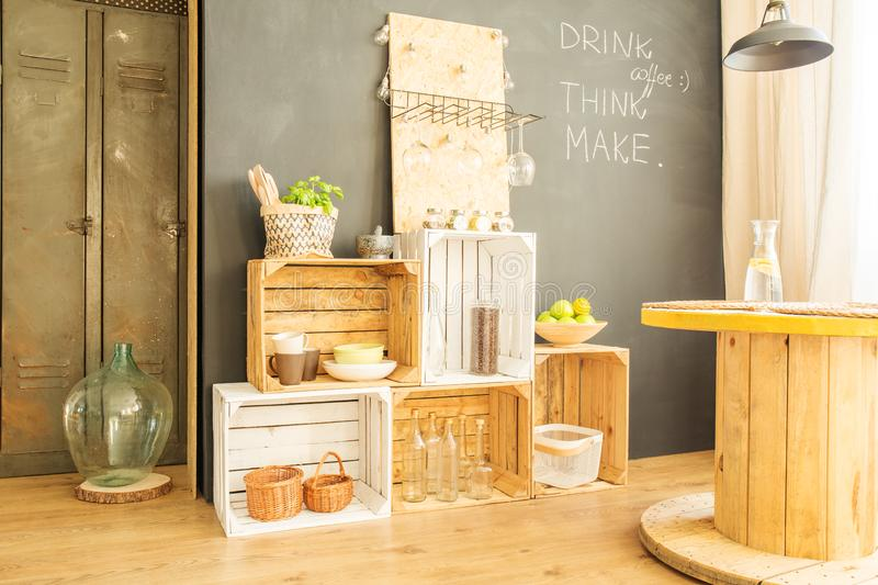 Crates against blackboard wall. Wooden crates with bottles and plates against blackboard wall stock image