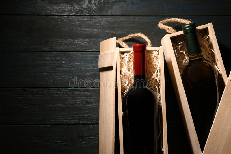Crates with bottles of wine on wooden table, flat lay. Space for royalty free stock image