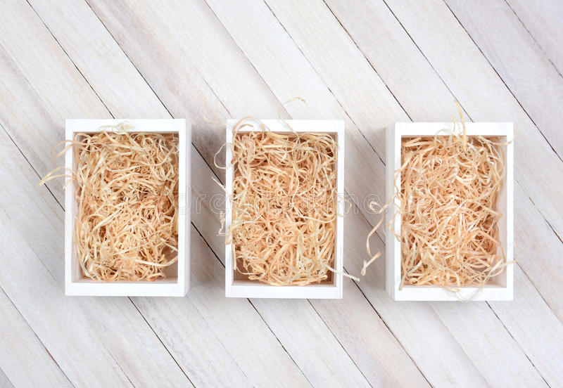 Crates with straw. High angle shot of three wood crates filled with straw on a rustic wood table. Horizontal format with copy space stock photos