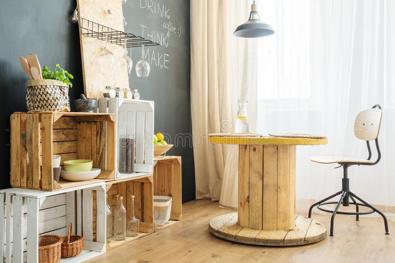 Crates and table in a room. Crates with accessories and wooden table in a room with blackboard wall stock photos