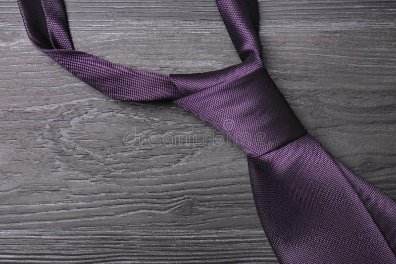 Cravate en soie pourpre élégante sur la table en bois gris-foncé images libres de droits
