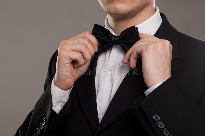 Cravatta a farfalla di tocchi delle mani dell'uomo immagini stock libere da diritti