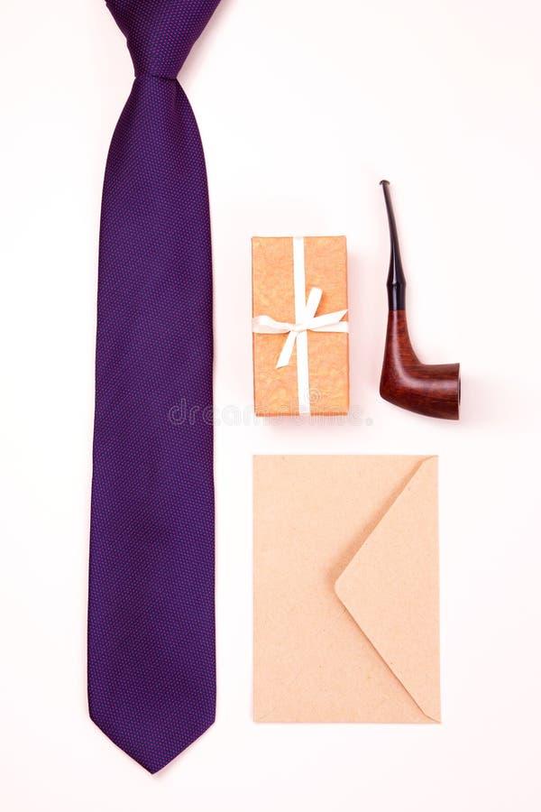 Cravatta per collo viola, scatola regalo con nastro bianco, busta di carta marrone e tubo per tabacco da fumo con spazio di copia fotografie stock libere da diritti