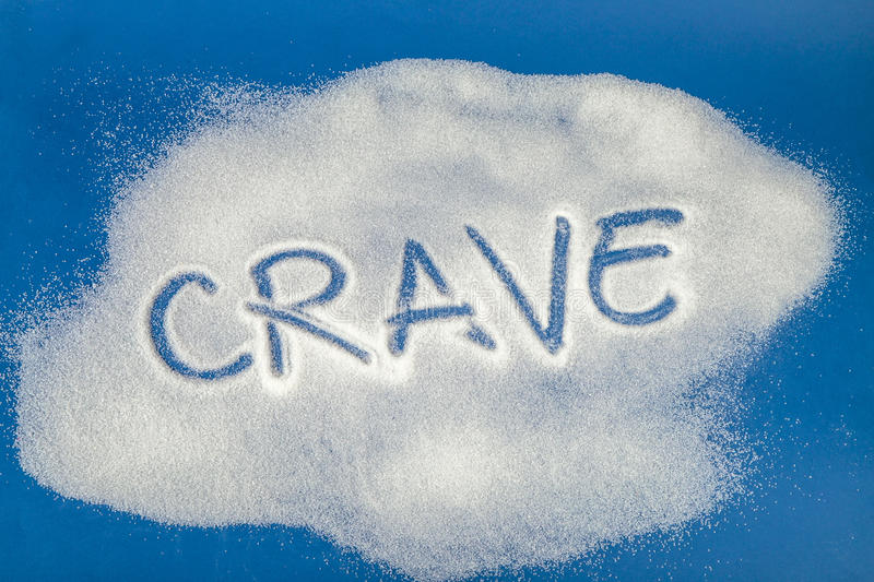 CRAVE written with sugar. Sugar on a blue background with warning message CRAVE written on it. Health concept. Diabetes hazard royalty free stock photo