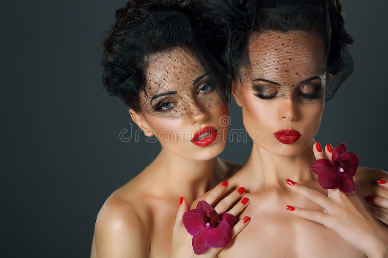 Craving. Aspiration. Two Seductive Fervent Women with Flowers. Passion. Two Seductive Fervent Women with Flowers royalty free stock image