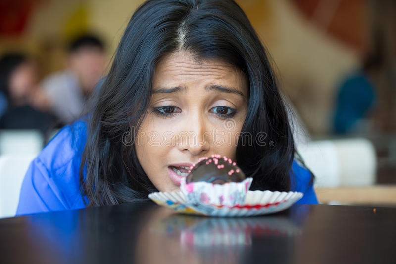 Craving hunger. Closeup portrait of desperate woman in blue shirt craving fudge with pink sprinkles dessert, eager to eat, isolated indoors background royalty free stock photos
