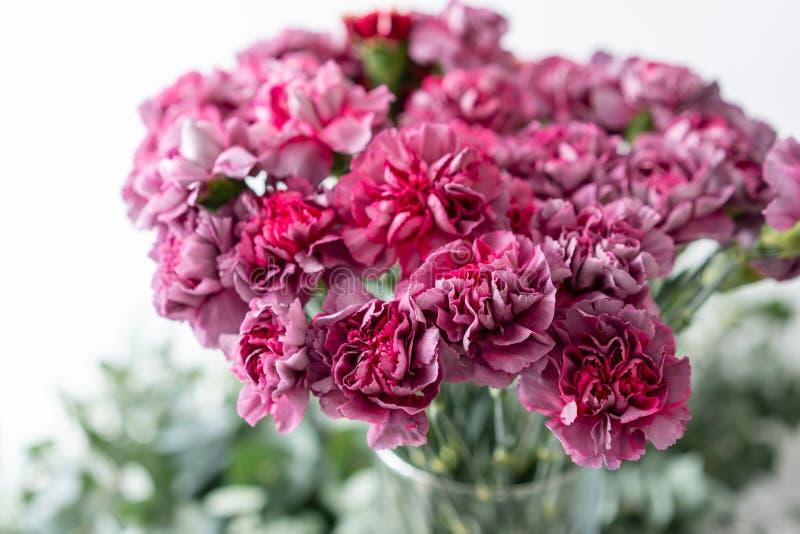 Cravo violeta lilás incomum do grupo no vaso de vidro Flores do ramalhete no fundo claro wallpaper fotografia de stock