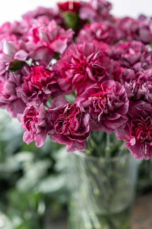 Cravo violeta lilás incomum do grupo no vaso de vidro Flores do ramalhete no fundo claro wallpaper fotografia de stock royalty free