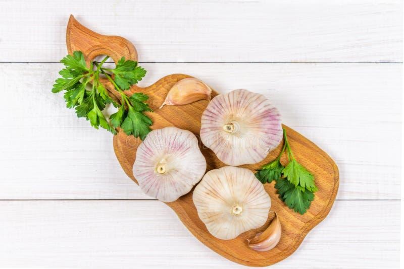 Cravos-da-índia de alho e bulbo do alho em uma placa de madeira em um fundo branco Vista superior fotos de stock royalty free