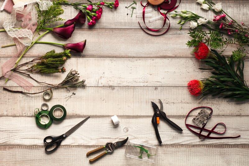 Cravos, rosas vermelhas, callas roxos em uma tabela de madeira em um florista fotos de stock royalty free