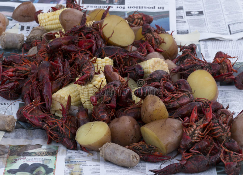 Crawfish on table. Pile of crawfish, potatoes, corn and sausages on a table covered with newspaper royalty free stock photo