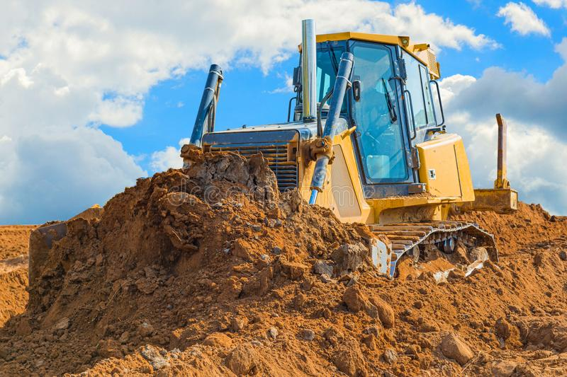 Crawler bulldozer - excavator with clipping path on a background with blue sky and clouds. work on construction site or sand pit. Scoop, industry, wheel royalty free stock photo