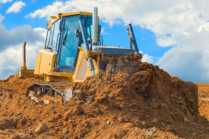Crawler bulldozer - excavator with clipping path on a background with blue sky and clouds. work on construction site or sand pit. Scoop, industry, wheel stock images